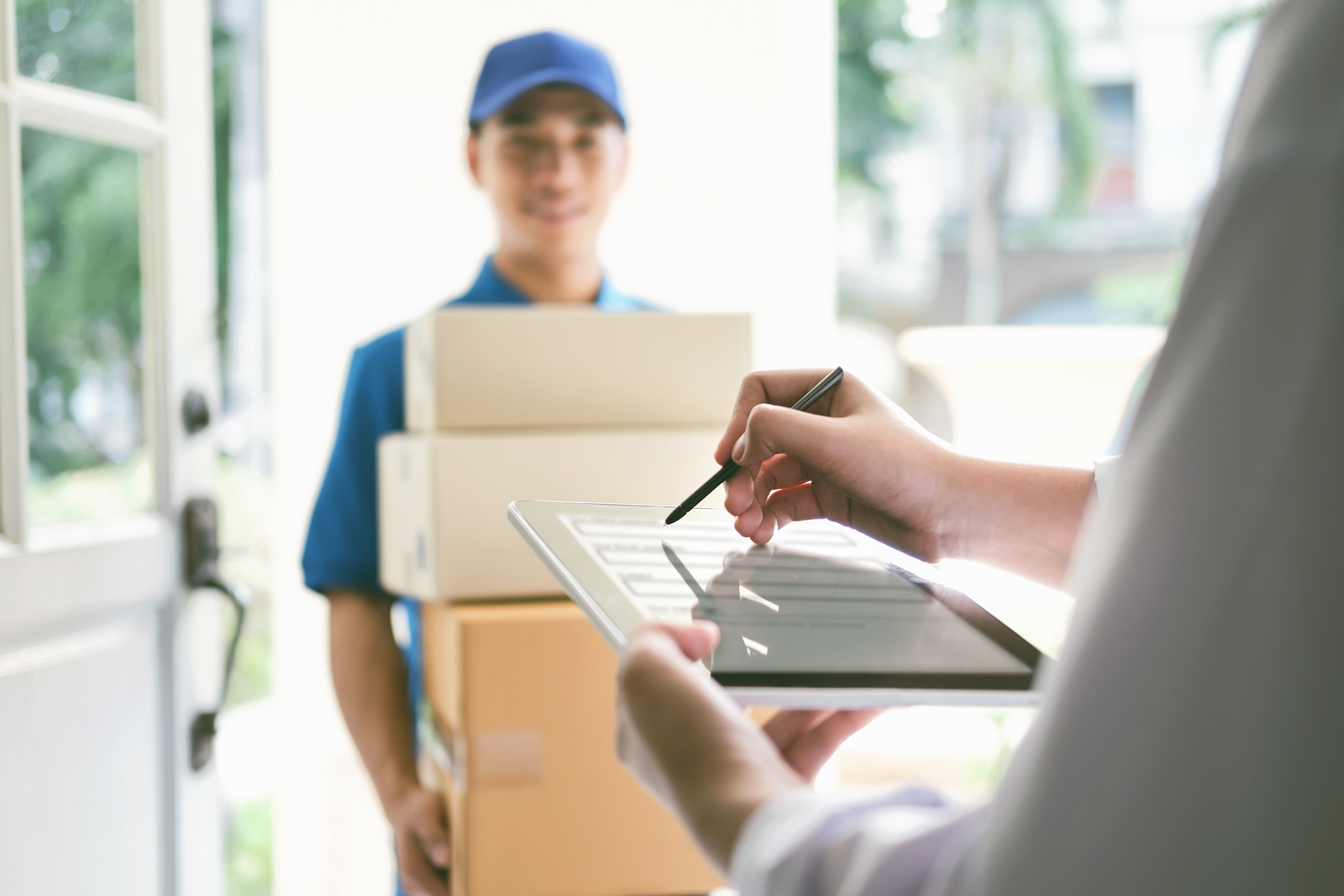 delivery mail people and shipping concept.Young woman sign in digital mobile phone after receiving parcel from courier at home.
